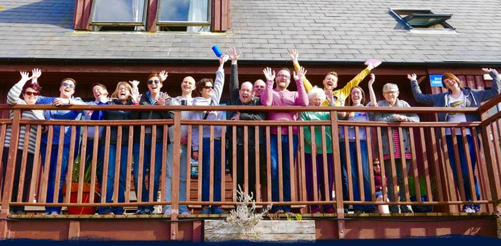 Large group of people taking a group photo on a balcony at Anglesey Outdoors