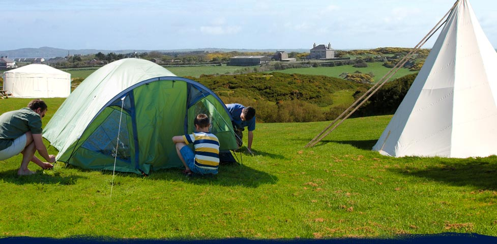 Campers  setting up atent on Anglesey Outdoor centre campsite