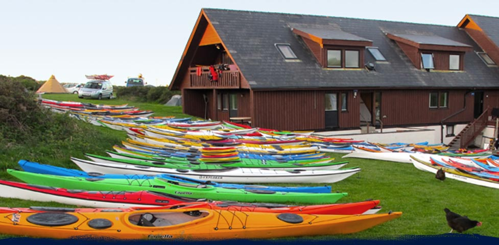 Colourful sea kayaks in row resting on the grass