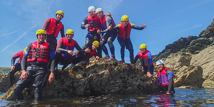 School group of people coasteering rocks on anglesey
